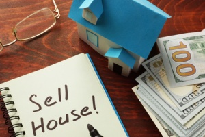 Notebook with the words Sell house  on the table.