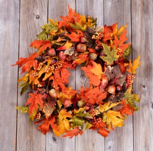 Wreath made of autumn leaves and acorns on rustic wooden boards