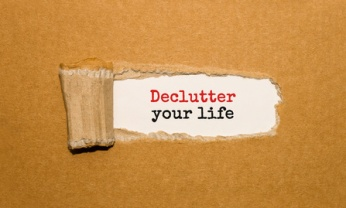 The text Declutter your life appearing behind torn brown paper